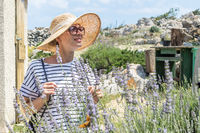 Beautiful blonde young female traveler wearing straw sun hat enjoying summer on Mediterranean cost strolling among lavander flowers on traditional costal village garden