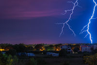 Two large and powerful lighting strikes crossing night blue sky