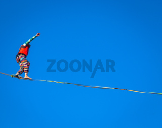 Slackline athlete during his performance. Concentration, balance and adventure in this dynamic sport.