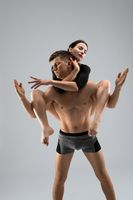 Shirtless male carrying young female on back