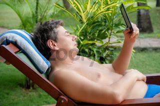 Mann im Urlaub liegt auf der Liege und liest in einem elektronischen E-Book-Reader