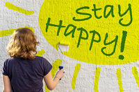 A young girl is painting a yellow sun and the green text STAY HAPPY on a white house wall