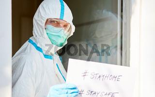 #stayhome #staysafe Botschaft gehalten von Mitarbeiter an Eingang einer Klinik
