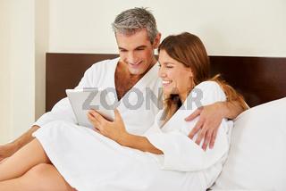 Paar im Hotel schaut auf Tablet Computer