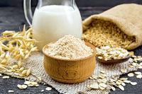 Flour oat in bowl on dark wooden board