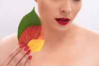 Pretty woman with Bared shoulders holds autumn colorful leaves near face. Perfect skin and Red lipstick on female lips. Beauty concept. Isolated on white background. Close up shot