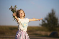 Beautiful little girl in the meadow with a bouquet of flowers. A child in a beautiful summer field.