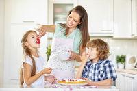 Kinder naschen beim Backen von Kuchen