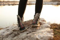 Fashion sneakers women's high bright leather and white rubber boots worn with jeans and both feet facing forward