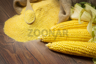 Ripe young sweet corn cob spoon and cornmeal