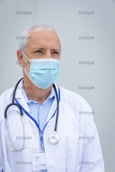 Senior male doctor wearing face mask against grey background