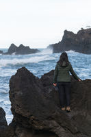 Woman seeing waves crashing on a rocky beach at Seixal, Madeira