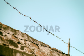 Fence with barbed wire on brick wall