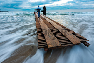 Two people go down the wooden sea pier into the distance, evening, long exposure