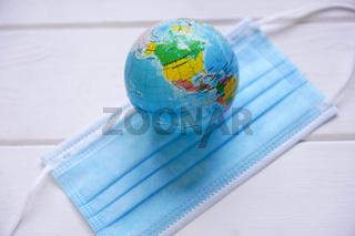 globe and medical face mask - global pandemic - corona covid
