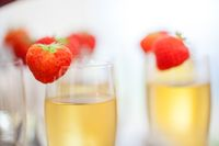 Close up of glasses of sparkling wine or champagne and strawberry