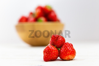 Little pile of strawberries with wooden bowl in background