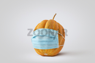Fresh natural organic pumpkin or melon vegetable in a medical protective face mask.
