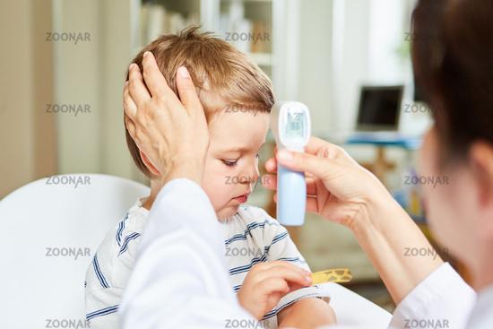 Kinderarzt und krankes Kind beim Fieber messen