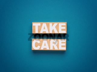 Two wooden blocks with inscription TAKE CARE on a blue background