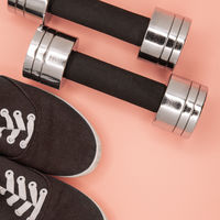 Metal small dumbbells and sneakers for training on a pink background.