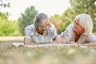 Paar Senioren liegt im Sommer im Garten