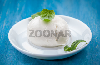 Portion of delicious buffalo mozzarella with basil leaves. Italian delicacy.