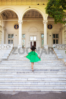 Summer vacation. A girl in a green dress stands on the stairs near the sanatorium. Chkalov in Odessa.