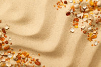 Ambers And Seashells On Sand Background