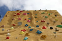 Detail of a climbing wall with a hold in the foreground. Climbing wall with on sky background