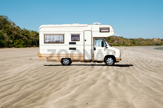 old camping bus, rv camper van at beach  -