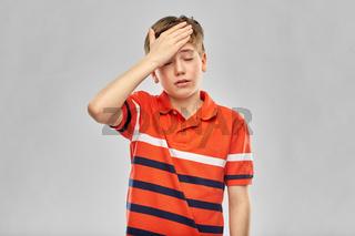 boy in red polo t-shirt having headache