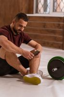 Handsome man sitting on a floor with smartphone in his hands and black and green tone fitness barbell, equipment for weight training concept. Sports equipment for training. Healthy lifestyle concept