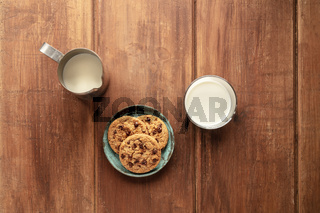 Chocolate chip cookies on a dark rustic wooden background, shot from the top with a milk jug and glass