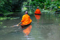 Buddhist monks paddle boat in the canal.