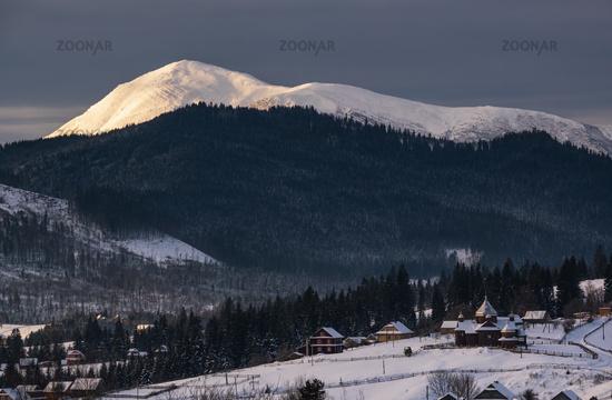 Small alpine village and winter snowy mountains in first sunrise sunlight around, Voronenko, Carpathian, Ukraine.