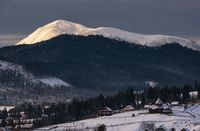 Small alpine village and winter snowy mountains in first sunrise sunlight around, Voronenko, Carpathian, Ukraine.