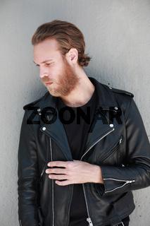 Vertical portrait of handsome bearded man, wearing biker leather jacket. Posing outdoor.