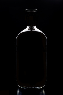 An empty liquor bottle in silhouette with reflection, isolated on black.