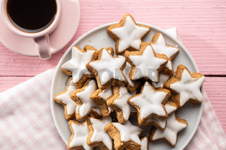 Icing gingerbread stars. Traditional Christmas cookies on pink wooden table.