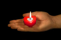 Heart shaped candle in hand