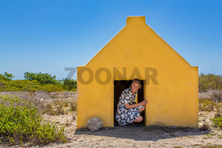 Woman entering yellow slave house at coast