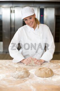 Baker kneading dough in bakery or bakehouse