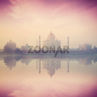 Vintage retro hipster style image of Taj Mahal on sunrise sunset reflection in Yamuna river panorama in fog