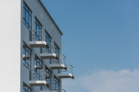Small balconies on the Bauhaus building in Dessau on clear day with blue sky
