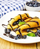 Pancakes with blueberries and chocolate on wooden board