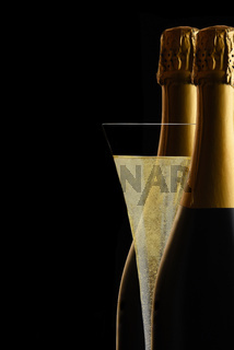 A Champagne Flute between two bottles of Sparkling Wine against a black background..