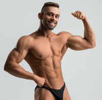 Dark-haired muscular athlete shot against gray wall
