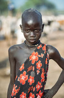 MUNDARI TRIBE, SOUTH SUDAN - MARCH 11, 2020: Kid in traditional garment with floral ornament keeping hand on waist and looking at camera while living in Mundari Tribe village in South Sudan, Africa