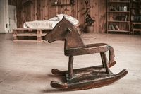 Antique wooden toy horse on the floor of spacious bedroom. Happy childhood memories concept